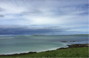 The Isle of Boreray, seen as two low humps with a beach in between when viewed from the spot on North Uist. Alatair and Verene paddled the 2 miles out from the point by Siabaigh, Isle of Berneray, jutting out on the right.Photo: Alastair McIntosh.